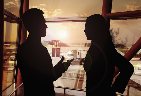 Two business people talking in the airport, Silhouette