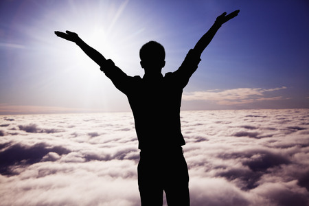 Silhouette of young man with arms raised with clouds and sky in the background photo