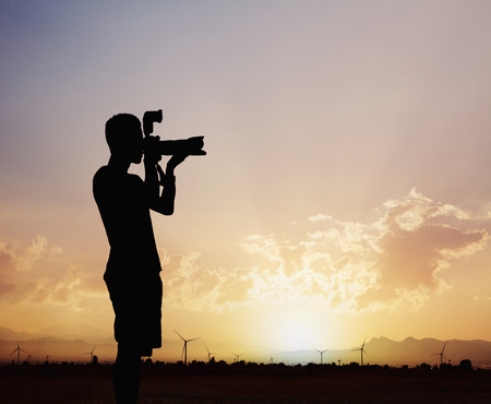 above 25: Silhouette of man taking photos with his camera at sunset with a dramatic sky Stock Photo