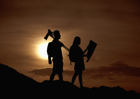 Silhouette of two people hiking and carrying camera and a map in nature at sunset photo
