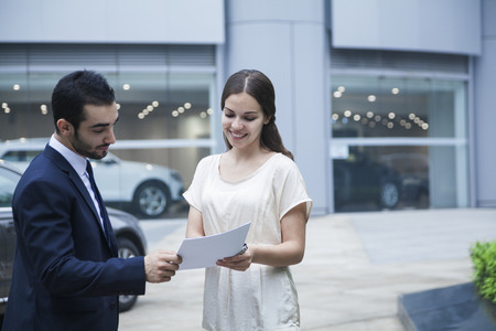 Car salesman and young woman looking over the paperwork at a car dealership Stock Photo