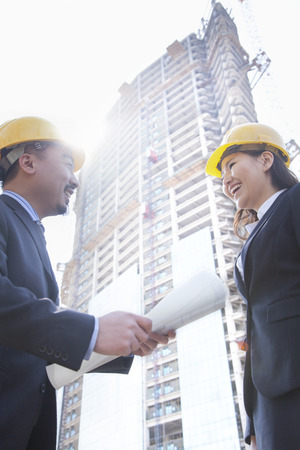 three day beard: Two architects smiling at a construction site holding blueprint