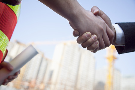Close up of architect and building contractor shaking hands  Imagens