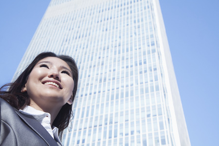 above 21: Portrait of young businesswoman by Chinas world trade center building in Beijing Stock Photo