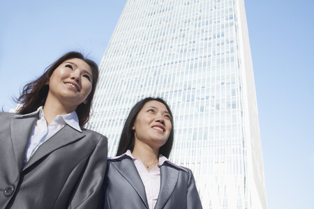 Two businesswomen standing in front of Chinas world trade center in Beijing 版權商用圖片
