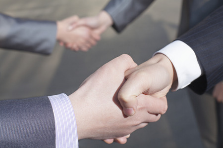 above 21:  Close up of four business people shaking hands