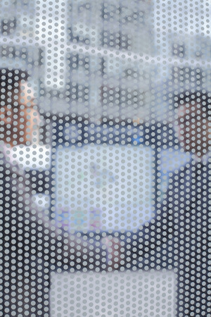 above 30: Two business people shaking hands seen through transparent glass