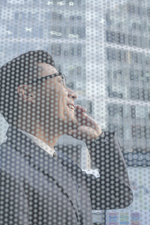 other side of: Businessman on the phone on other side of glass wall
