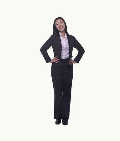 above 21: Portrait of smiling  young businesswoman with hands on hips looking at camera, full length, studio shot Stock Photo