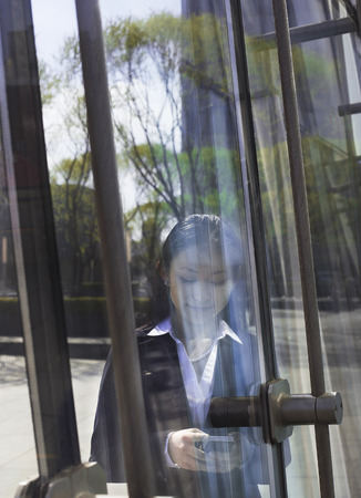 other side of: Young smiling businesswoman using the phone on the other side of a glass door