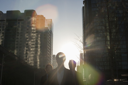 above 21: Three business people walking down a city street with sunlight at their back, lens flare