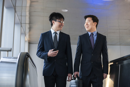 Two smiling businessmen coming up the escalator together photo