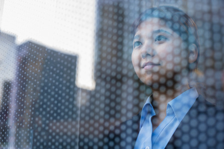 reflection: Businesswoman looking out through window, reflection of the city on the glass