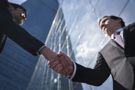 Two businessmen shaking hands in Beijing, China, view from below