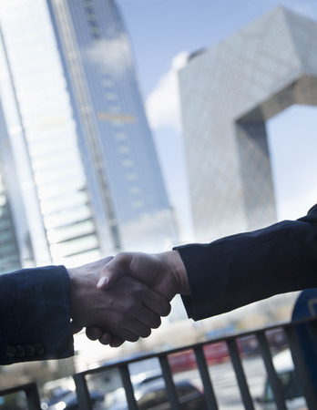 griping: Close up of two business people shaking hands by the CCTV Building in Beijing