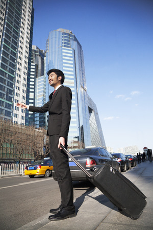 hailing: Young Businessman with luggage on the street hailing a cab