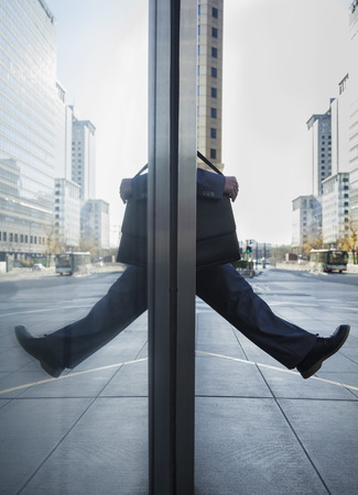 stepping: Businessman stepping out into the street, reflection in the glass of the building