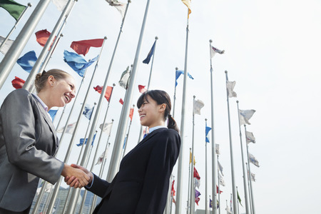 griping: Two young businesswomen shaking hands outdoors   Stock Photo