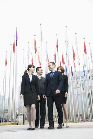 above 21: Four smiling young business people standing outside, flags flying in the background