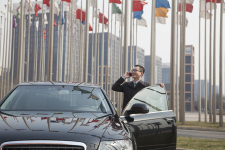 above 30: Smiling Businessman on the phone getting into his car