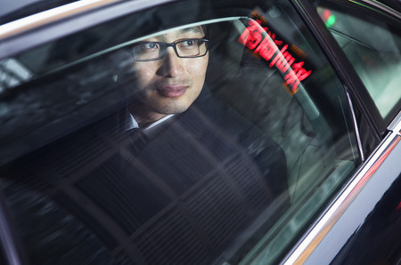 above 30: Contemplative businessman looking through car window at the night  Stock Photo