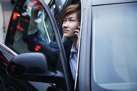 exiting: Businesswoman exiting car while on the phone