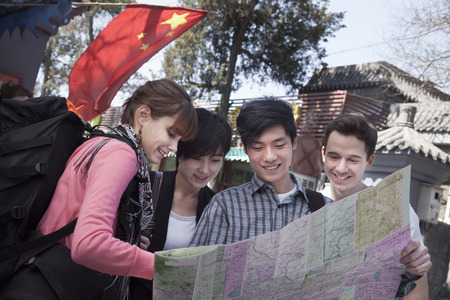 above 21: Four young people looking at map. Stock Photo
