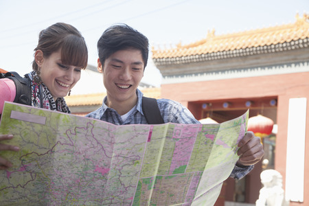 above 21: Young couple looking at map.  Stock Photo