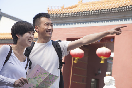 above 21: Young couple looking at map and pointing.  Stock Photo