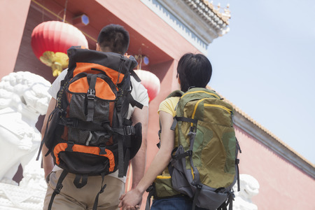 above 21: Young couple with backpacks, holding hands.