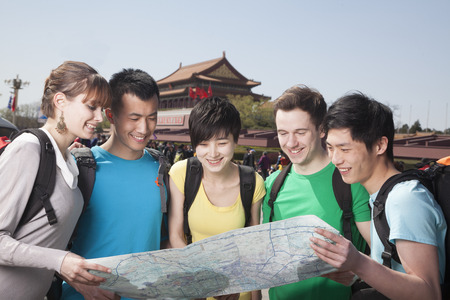 above 21: Five people looking at map with Tiananmen Square in background. Stock Photo