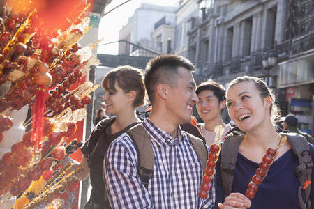 candied fruits: Young people buying candied haw.