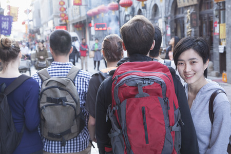 above 21: Group of young people walking down street, woman looking over shoulder. Stock Photo