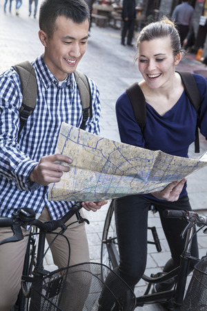 above 21: Young man and woman on bicycles, looking at map. Stock Photo