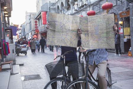 above 21: Young man and woman on bicycles holding maps.