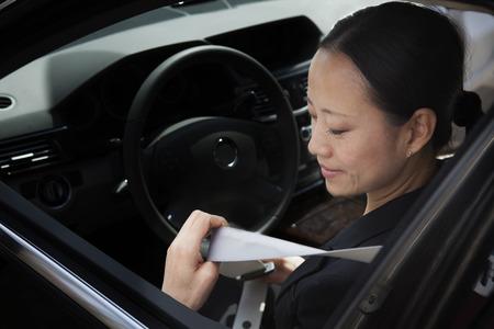 fastening: Mature businesswomen in car fastening seatbelt.