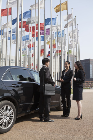 flagpoles: Three businesspeople meeting outdoors with flagpoles in background