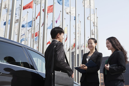 flagpoles: Three businesspeople meeting outdoors with flagpoles in background.
