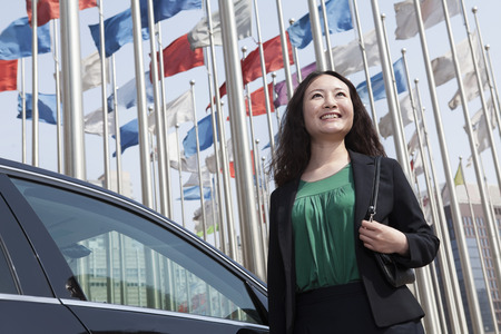 flagpoles: Businesswomen standing near car flagpoles in background.