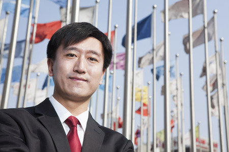 flagpoles: Businessmen portrait with flagpoles in background. Stock Photo