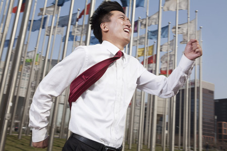 flagpoles: Businessmen running and smiling with flagpoles in background.