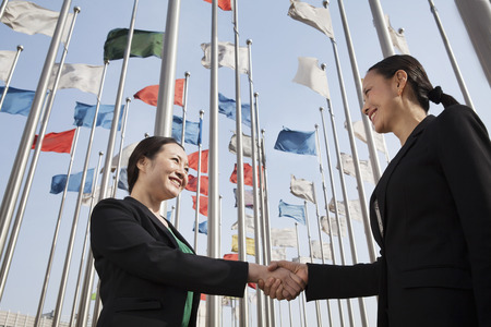 Two businesswomen shaking hands with flags in background. Stock Photo