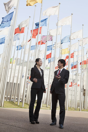 flagpoles: Two businesspeople meeting outdoors with flagpoles in background. Stock Photo