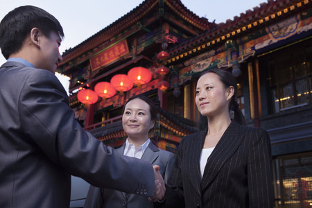 above 25: Three businesspeople meeting outdoors with Chinese architecture in background.