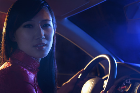 above 25: Portrait of young, beautiful woman in traditional clothing driving at night in Beijing