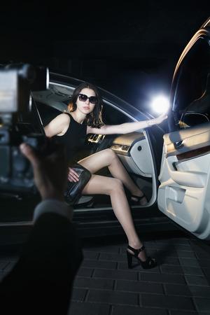 hombre rojo: Paparazzi tomar una foto de una joven y bella mujer saliendo de un coche en un evento de alfombra roja