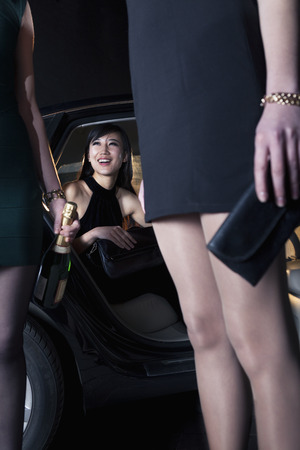 above 18: Three beautiful women arriving at a red carpet event in a car, night, Beijing Stock Photo