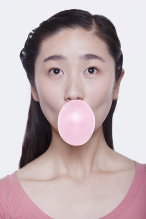 Young playful woman blowing a bubble out of bubble gum, studio shot