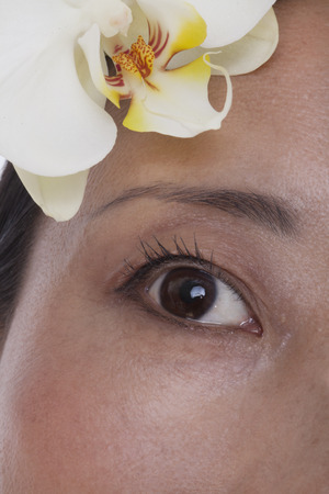 above 30: Extreme close up of eye and a white flower, studio shot