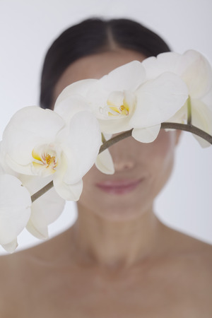 obscured: Shirtless smiling woman behind a bunch of beautiful white flowers, obscured face, studio shot